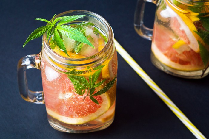 A clear beverage with a grapefruit slice and a marijuana leaf in it