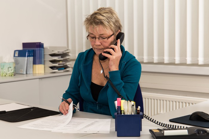 Woman at desk in office looking at papers while on phone.