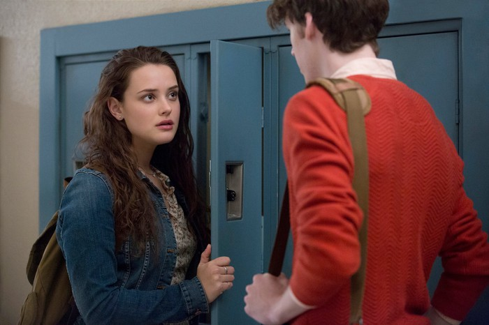 A teen boy and girl talking to each other in front of lockers.