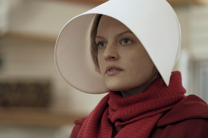 A woman dressed in red, wearing a long, white hat in a scene from The Handmaid's Tale.
