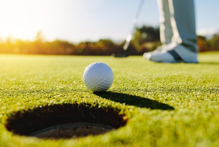 A golf ball near a hole