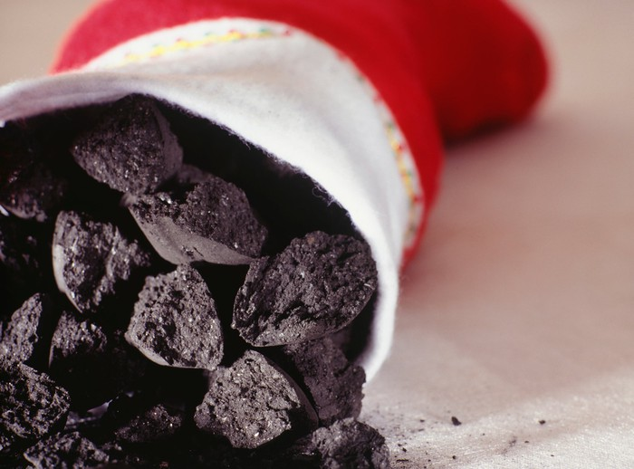 A close-up of lumps of coal being placed inside of a Christmas stocking.
