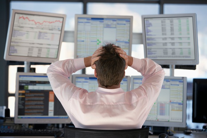A frustrated stock trader grasping his head while looking at losses on six computer monitors.