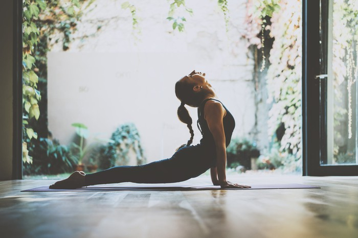 Woman doing yoga pose in a room with glass doors open to a courtyard filled with plants