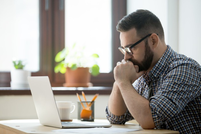Man at laptop with serious expression.
