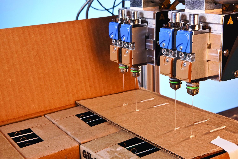Nordson equipment dispensing adhesive on a cardboard box