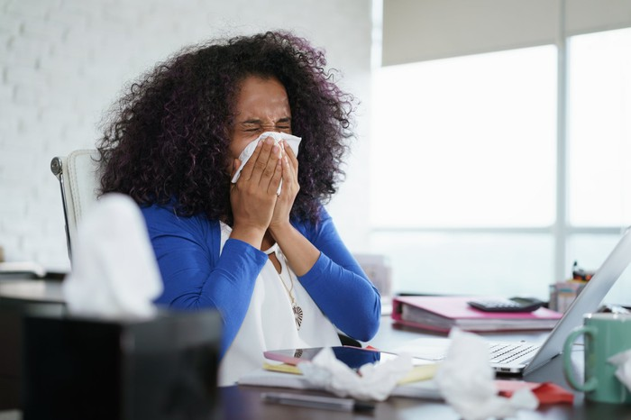 Woman blowing nose at desk