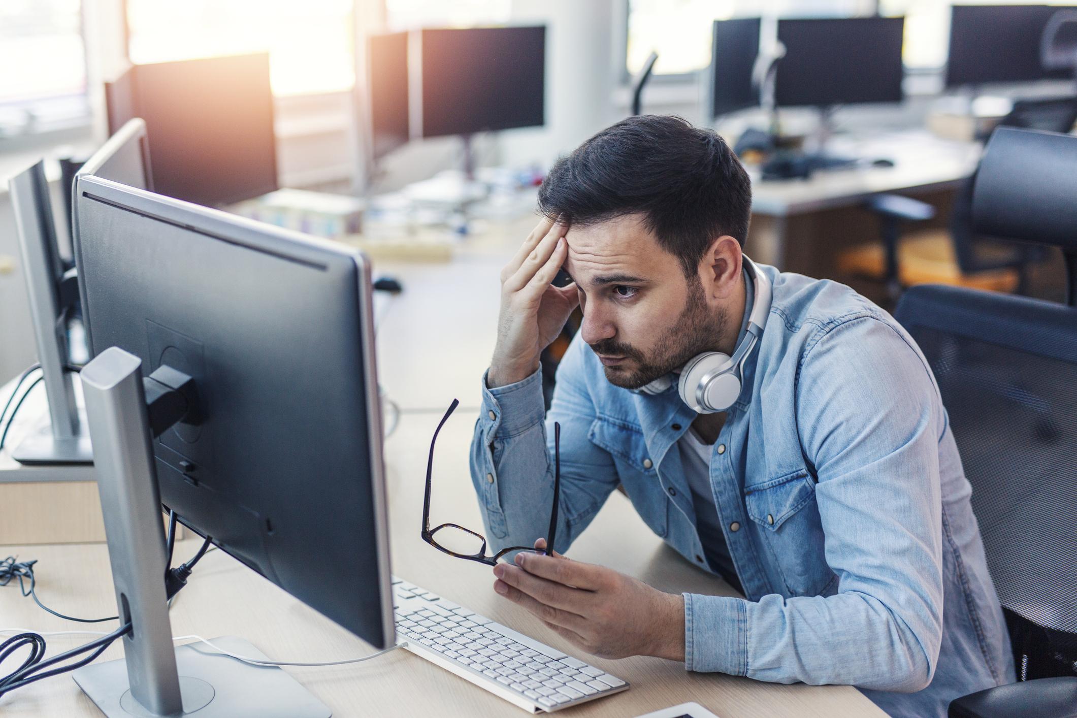Man at computer frowning