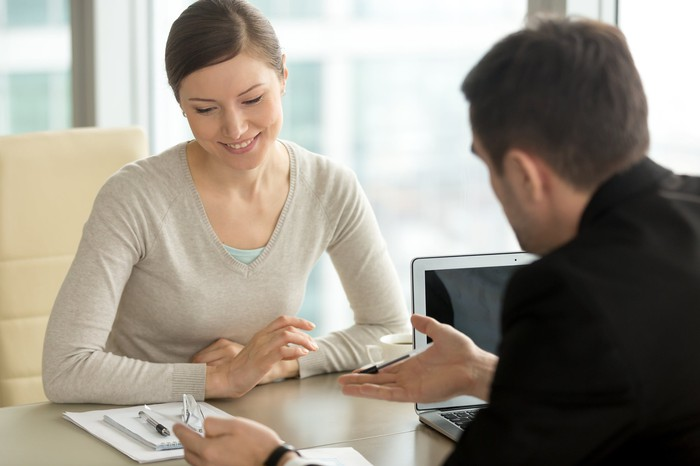 Woman sitting across from gesturing man at desk