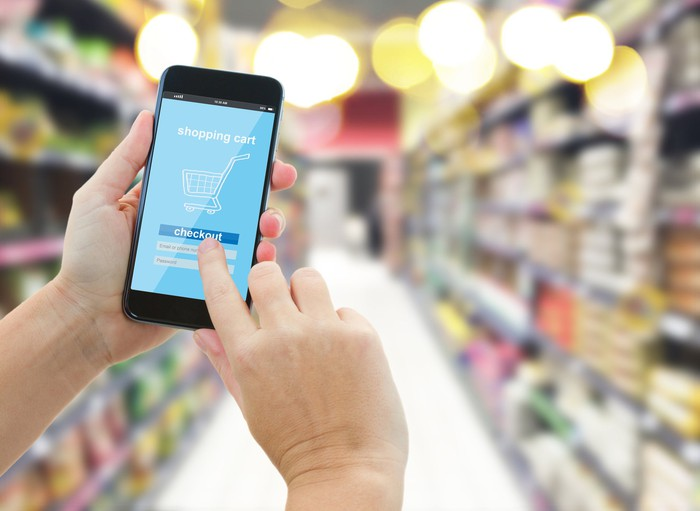 A hand taps a shopping cart icon on a cell phone of a person standing in a grocery aisle.