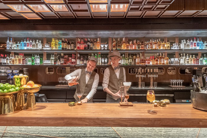 Two men are serving drinks at the new cocktail bar inside the New York Roastery.