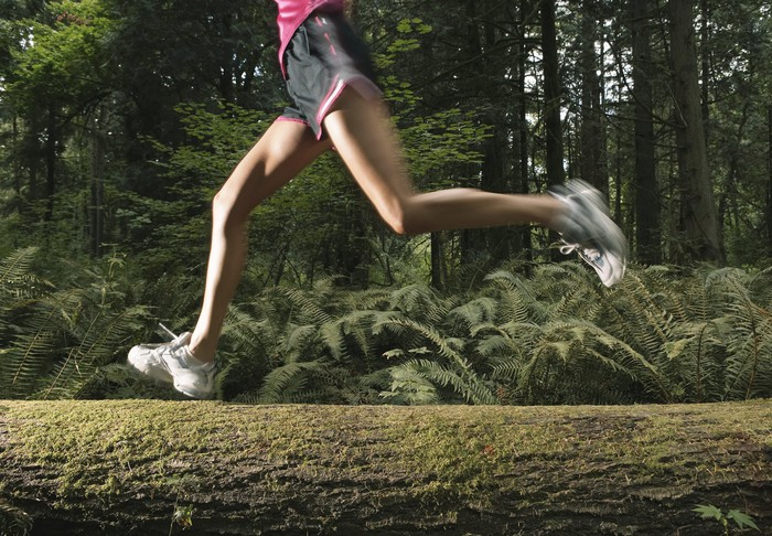 A woman jogging in the forest.