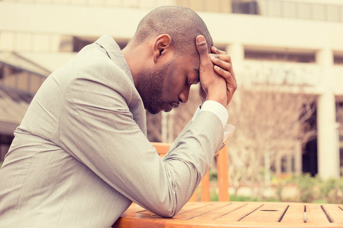 Man holding his head as if upset or stressed.