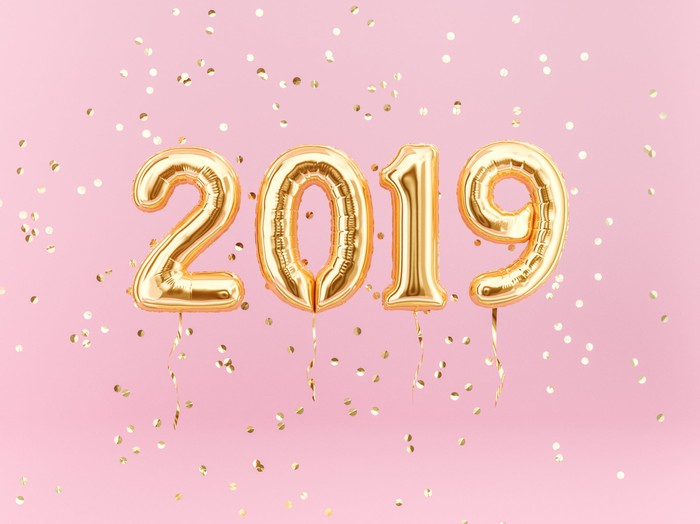 Gold balloons spelling out 2019 against pink background with gold confetti falling all around.