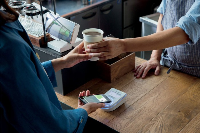 A person paying for cup of coffee using Apple Pay on a smartphone.