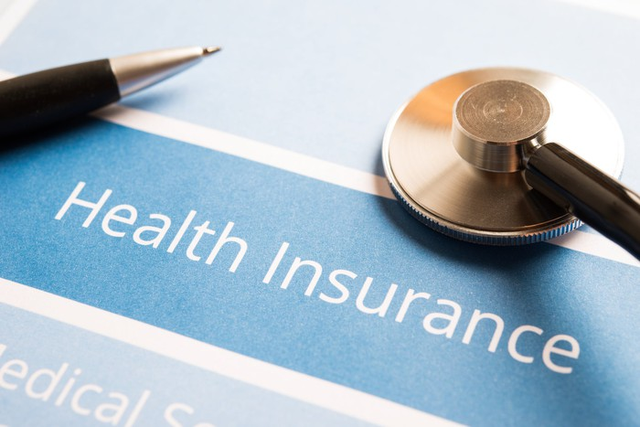 Health insurance document with a pen and a stethoscope on top