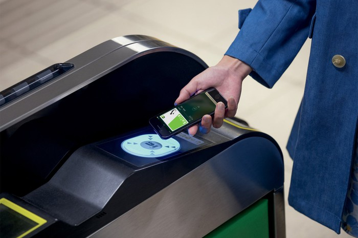 A woman holding an iPhone over a scanner using Apple Pay.