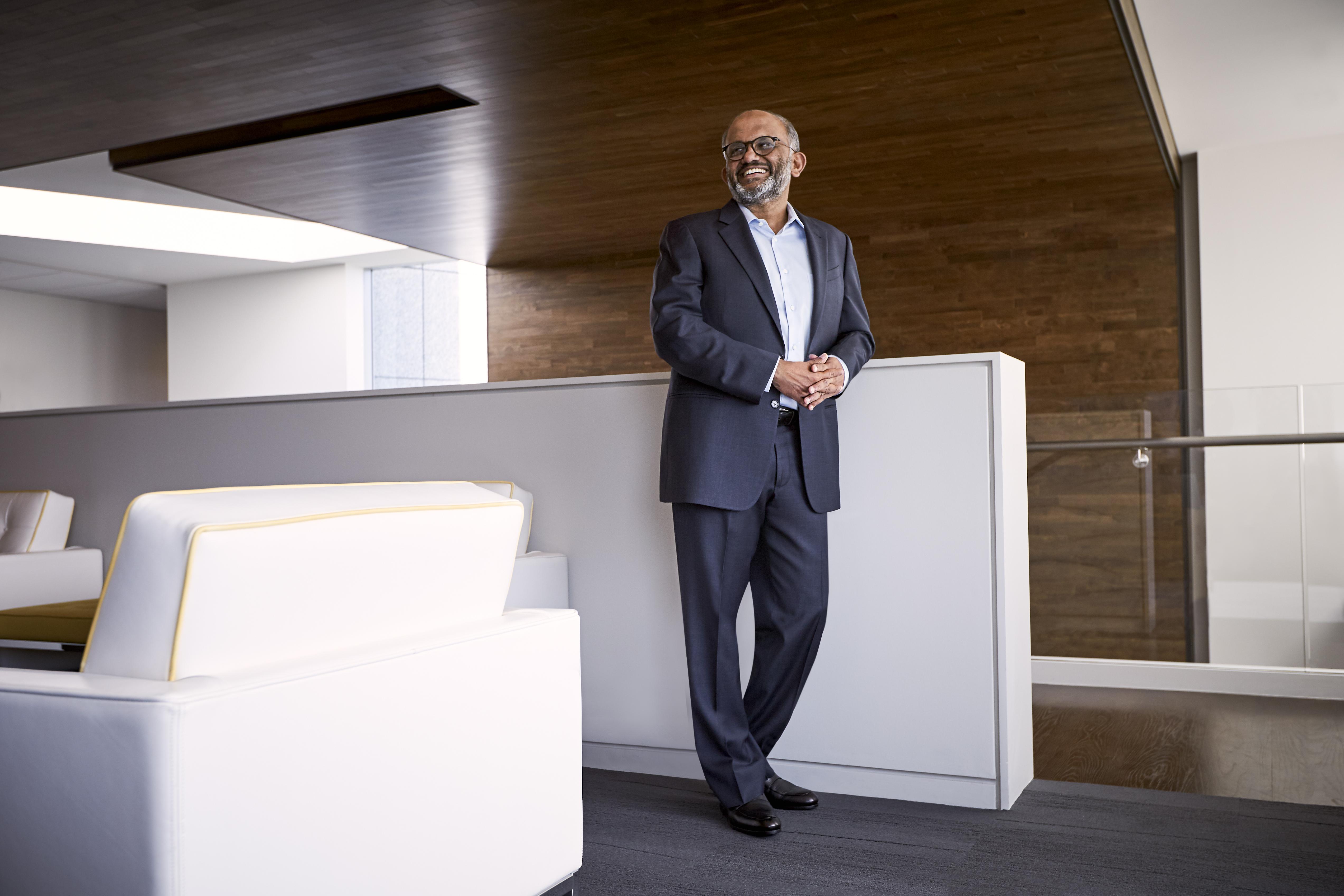 A smiling Adobe CEO Shantanu Narayen standing next to a white counter.