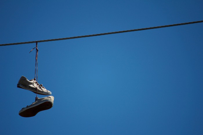 Pair of sneakers hanging from electrical wire
