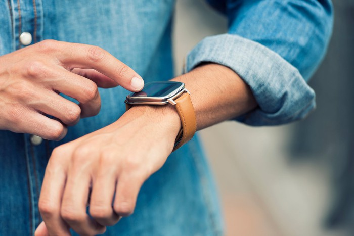 Person tapping their smartwatch.