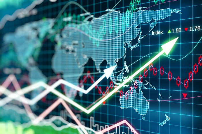 Stock market data overlaying a digital world map and indicating gains