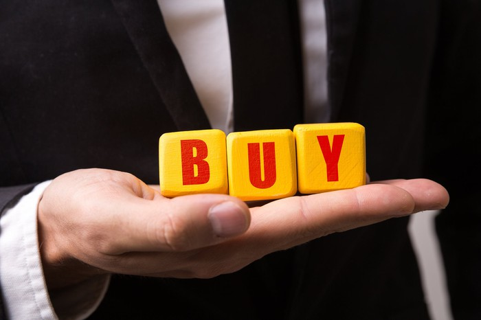 Yellow blocks spelling out the word buy in red letters on a man's hand.