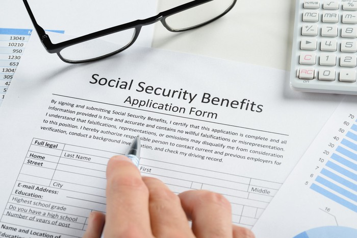 A hand filling out a Social Security benefits application form, which sits under a pair of glasses and a calculator.