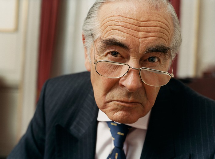 An angry senior man in a suit with a scowl on his face.