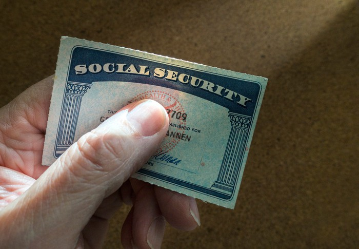 A senior person tightly gripping their Social Security card between their thumb and index finger.