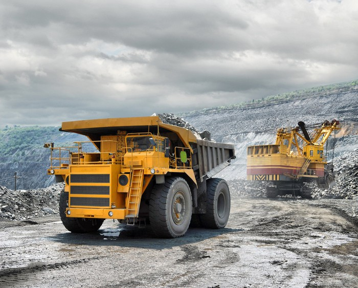 Loading of iron ore on a very big dump-body truck.