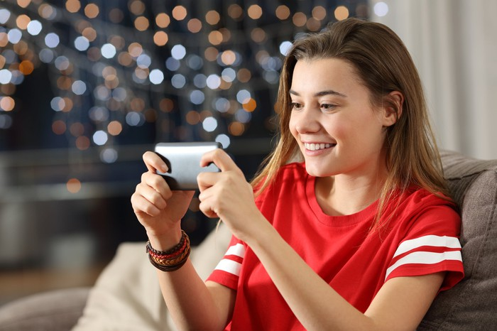 A teenage girl plays a video game on her smartphone while sitting in her living room.