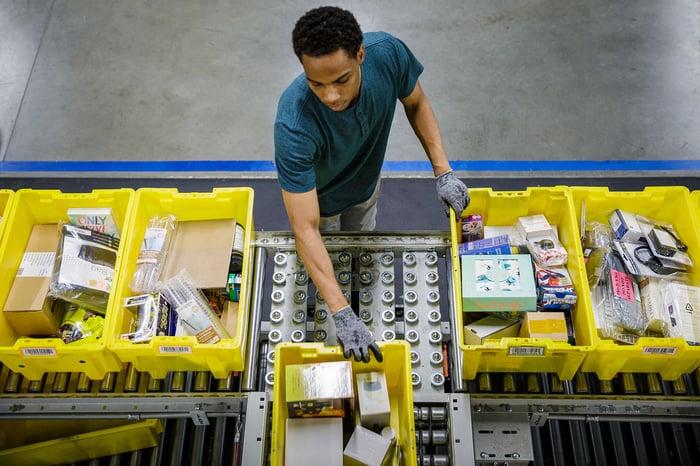 Amazon.com warehouse employee, seen from overhead, sorts yellow bins full of merchandise on a conveyor belt.