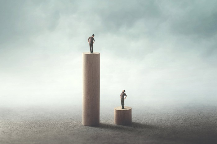 Two men on different size pedestals looking at each other.