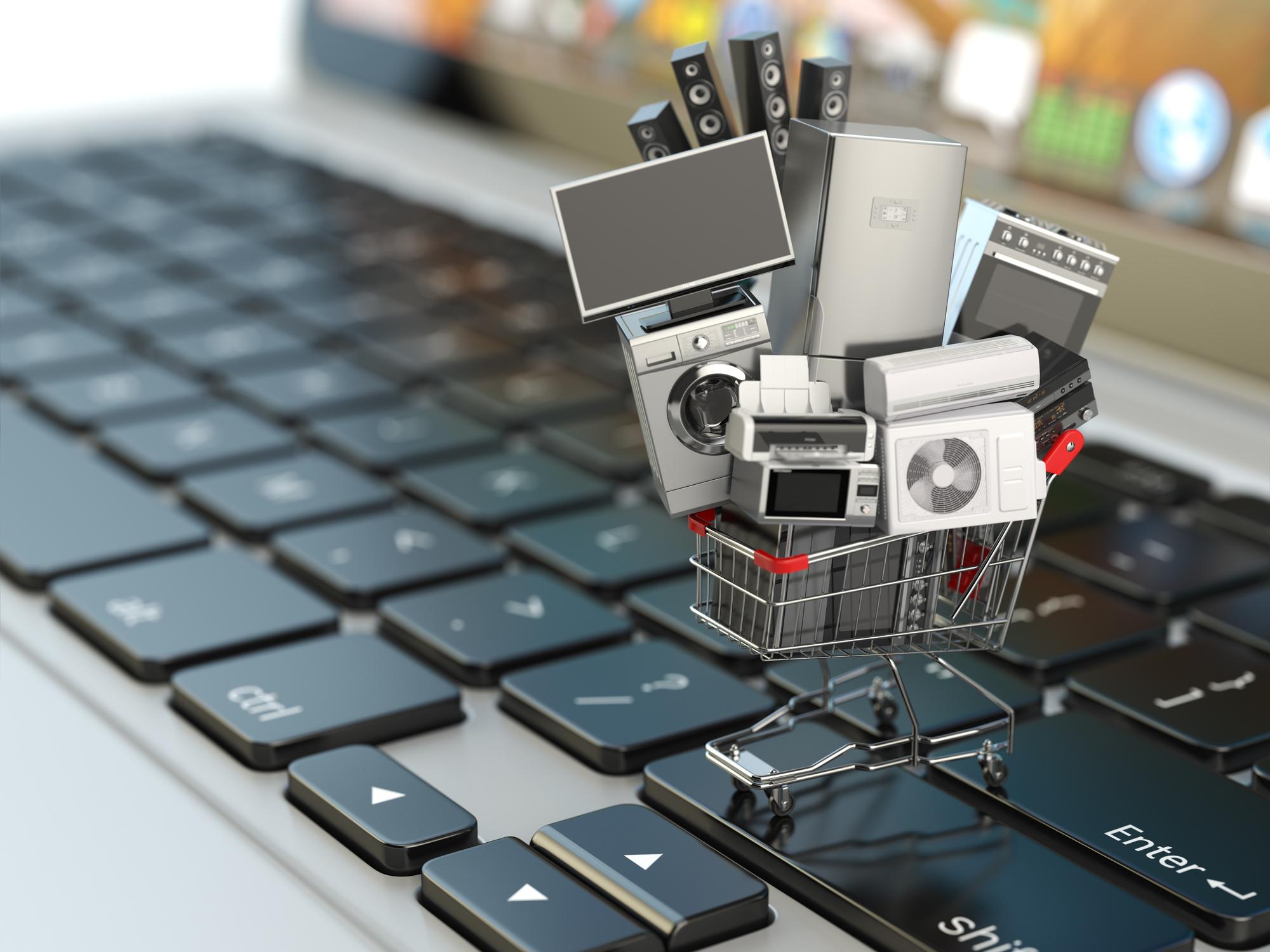Miniature shopping cart full of electronics on a keyboard