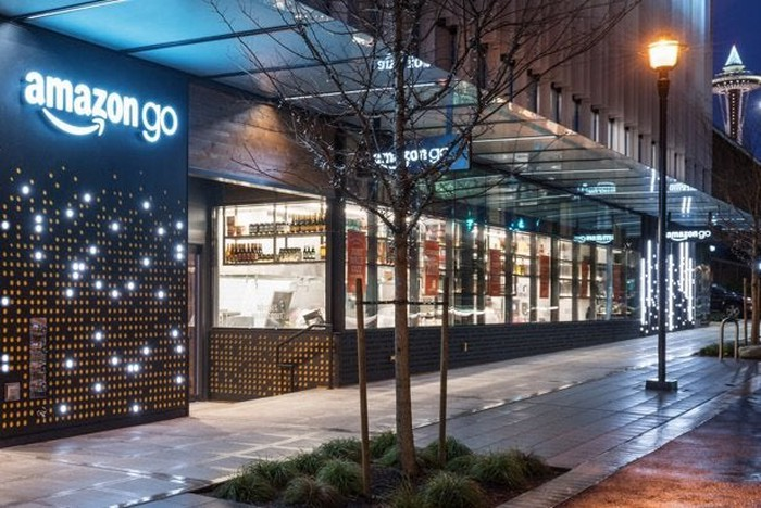 Exterior of Amazon Go store at night, with the Seattle Space Needle in the distance