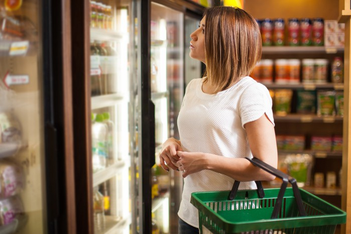 Young woman looking in refrigerated section of a convenience store