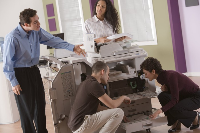 Several people trying to fix a Xerox machine