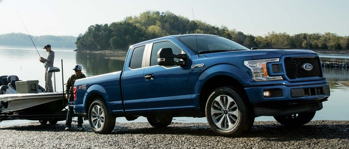 A dark blue Ford F-150 pickup truck pulling a fishing boat out of a lake.