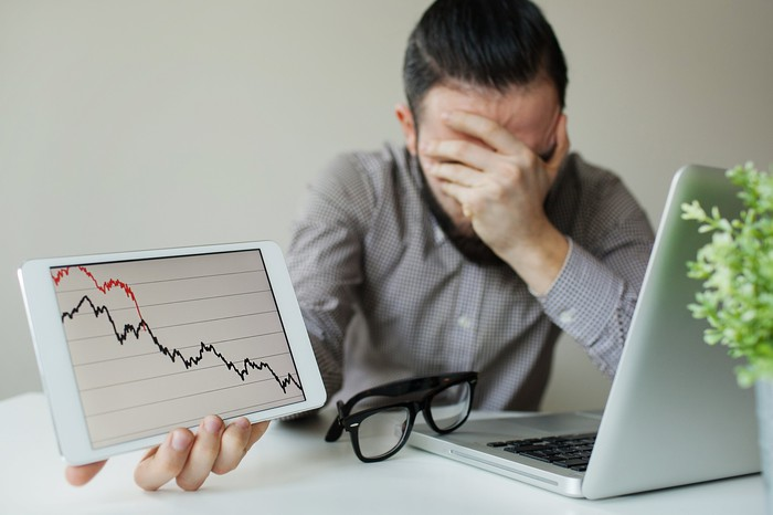 A frustrated investor covering his face with his left hand, while holding up a tablet that shows a plunging stock chart in his right hand.