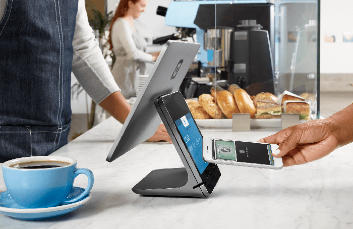 Customer using a smartphone at a Square Register to pay for coffee.