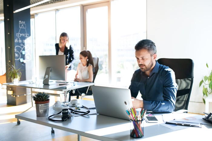 Three people working in an office