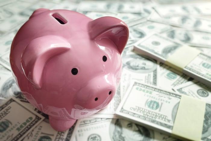 Piggy bank on stacks of money.