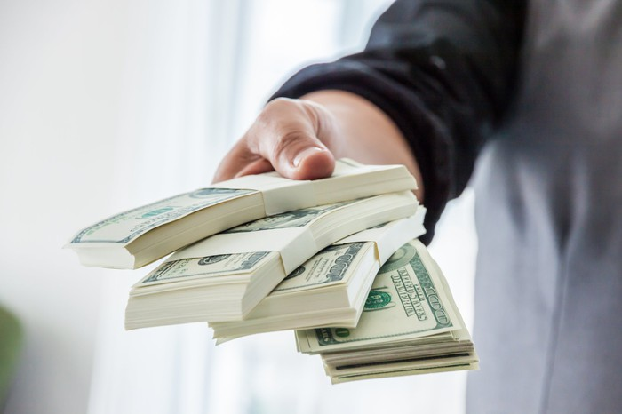 A man in a suit hands over a stack of money