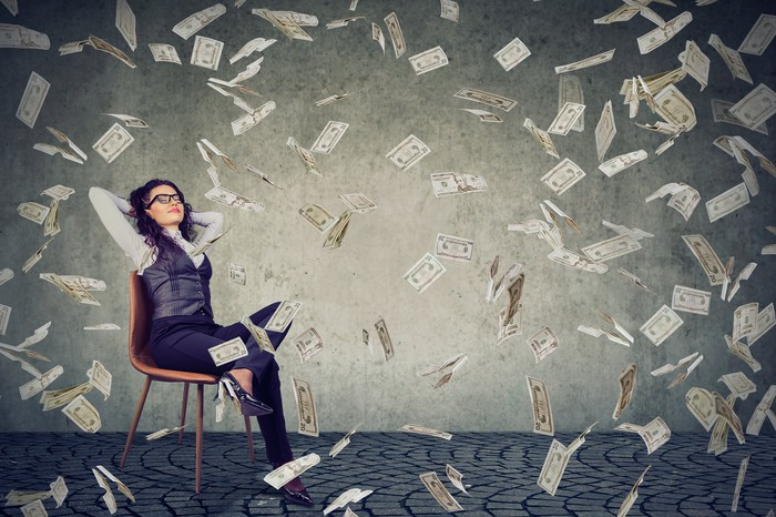 A woman sits in a chair as money falls down around her.