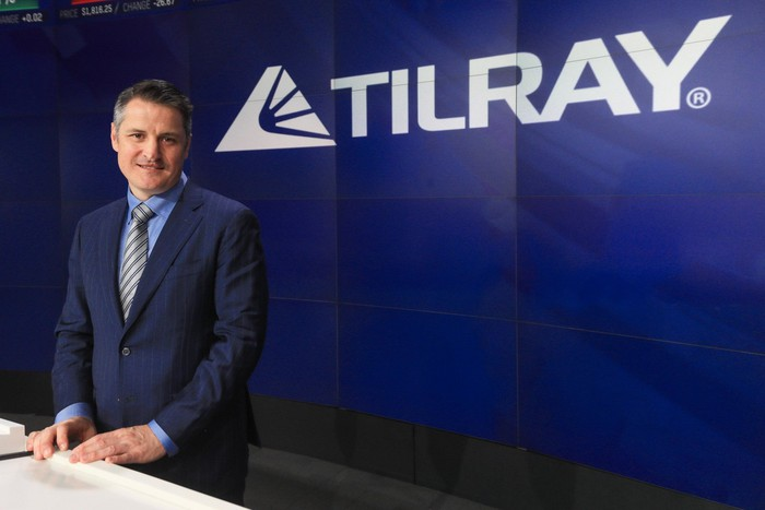 Person wearing suit standing at a desk in front of blue screen with Tilray logo on it.