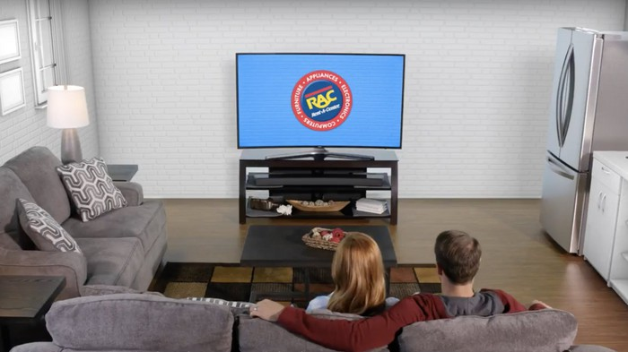 Two people sitting on couch watching a TV with the Rent-A-Center logo on it.