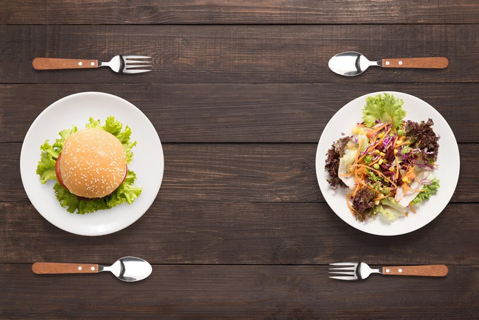 A burger on a plate flanked by a fork and spoon facing a salad on a plate flanked by a fork and spoon