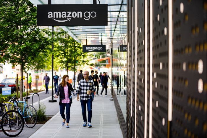 A woman and man walking on the sidewalk outside an Amazon Go store.