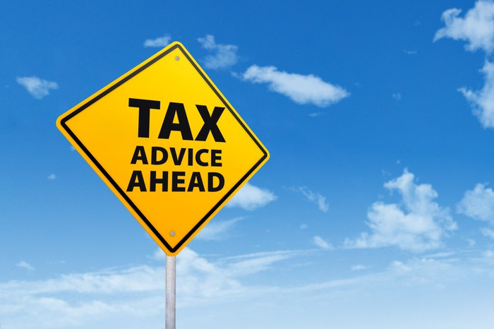 A yellow street sign says tax advice ahead, against a blue sky.