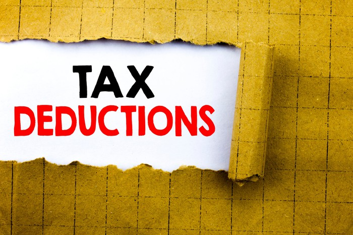 A yellow paper covering is peeled back to reveal the words tax deductions printed in red and black on a white background